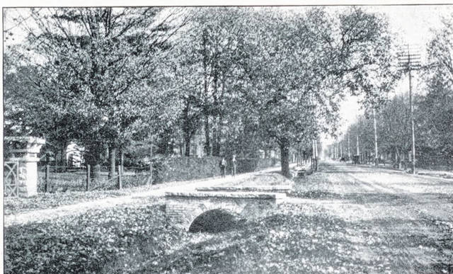 This is a circa 1910 postcard street scene (#A1030) looking east on Scioto Street from the intersection with Happersett Street. The stone post on the left edge of the photo marks the driveway entrance to the large house that is midway between Scioto and East Court streets. This is likely the same post visible in the Now photo. Note the stone bridge over the ditch that runs on the north side of the street. Horse and buggies are traveling the unpaved street.